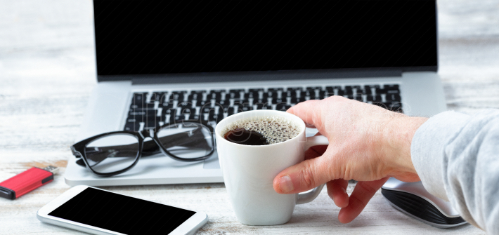 Male hand reaching for a cup of coffee with workstation technolo