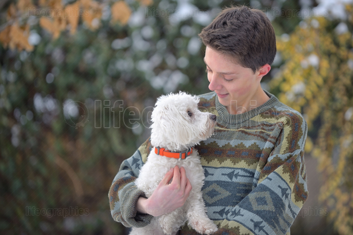 Maltese dog and teen boy on winter