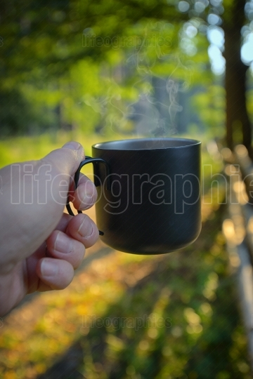 Man hand drinking coffee in morning