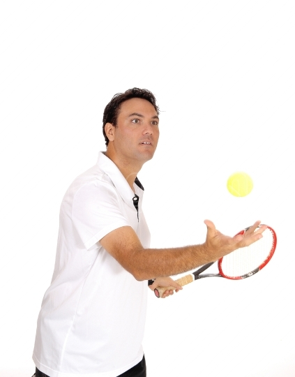 Man playing tennis in the studio with red ball