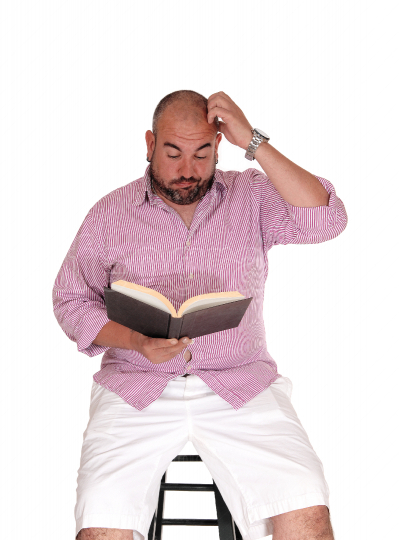Man reading a book and scratching his head