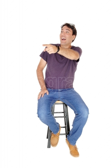 Man sitting and laughing, pointing finger