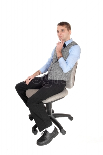 Man sitting in dress pants and vest, thinking