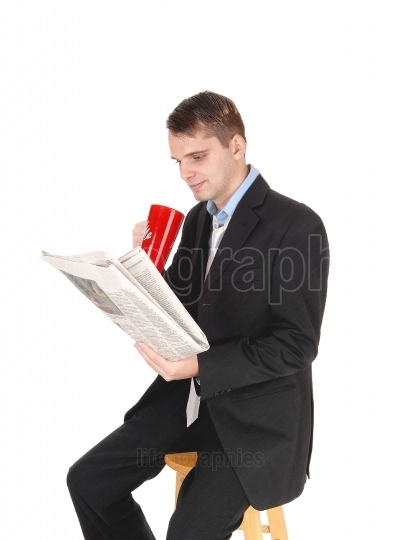 Man sitting in suit drinking and reading paper