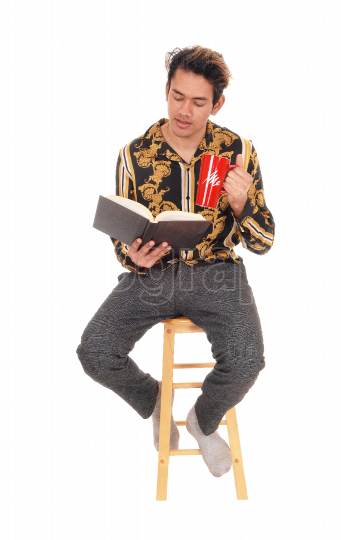 Man sitting on a chair with his coffee and reading