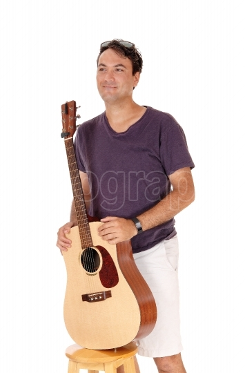 Man standing and holding his guitar, smiling