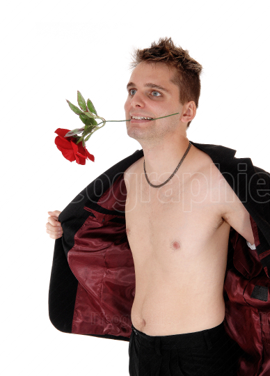 Man standing shirtless in an open jacket and a rose in his mouth