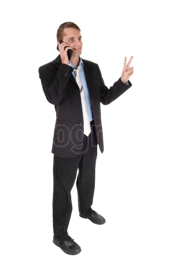 Man standing talking on phone with victory sign
