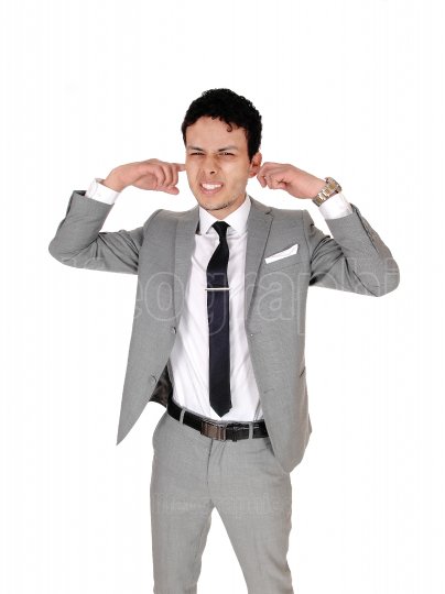 Man standing with his fingers in his ears