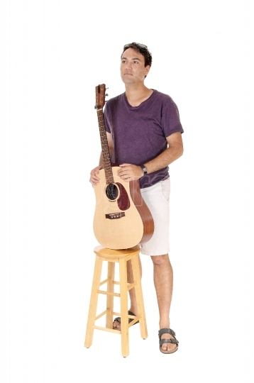 Man standing with his guitar behind a chair