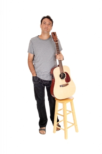 Man standing with his guitar holding it on a chair