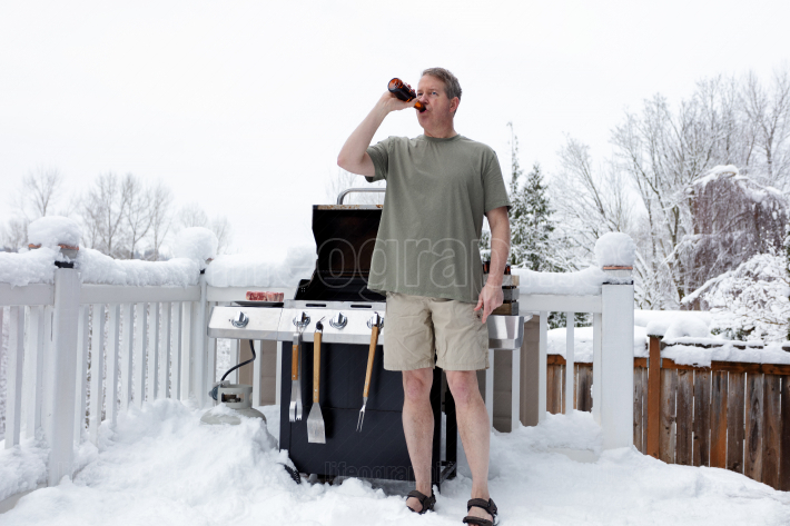 Mature man getting ready to grill while drinking beer during win