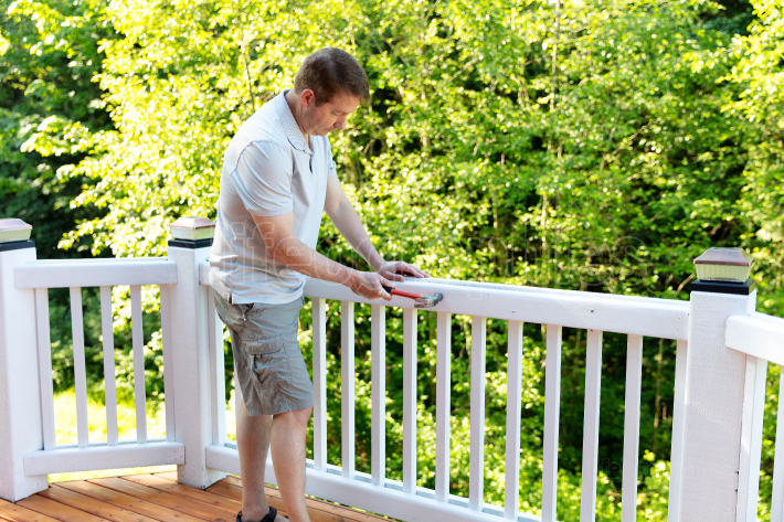 Mature man hammering nail into white railing of outdoor deck