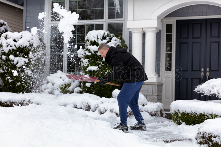 Mature man removing snow in front of home