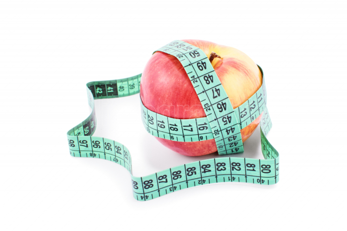 Measuring tape twisted around ripe apple