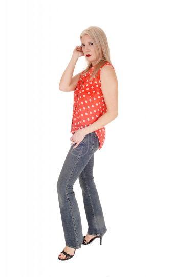 Middle age woman standing in profile in jeans