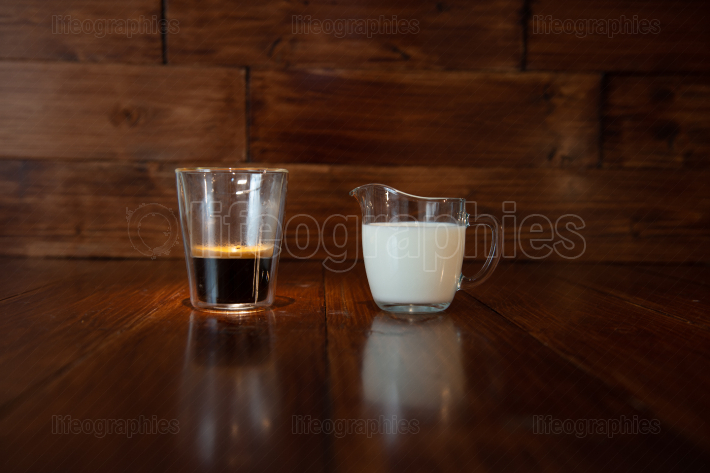 Milk in glass milk jug with a cup of coffee in a transparent glass