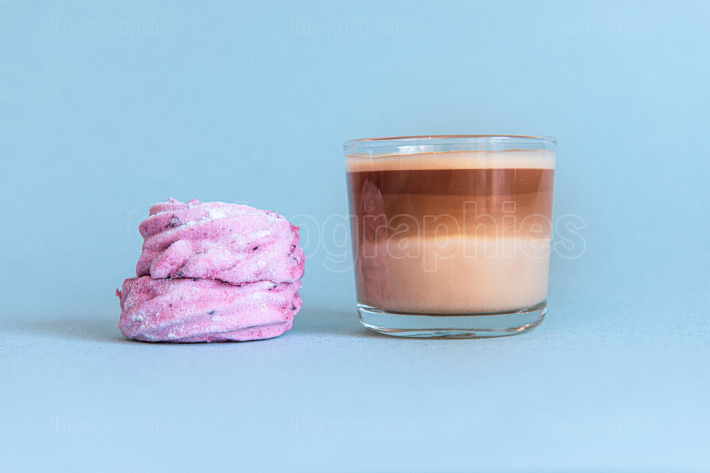 Mini cup of multilayer coffee in a glass cup on blue background