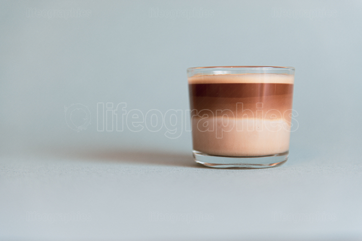 Mini cup of multilayer coffee in a glass cup on grey background
