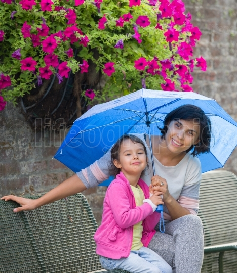 Mother and daughter on a bench with an umbrella