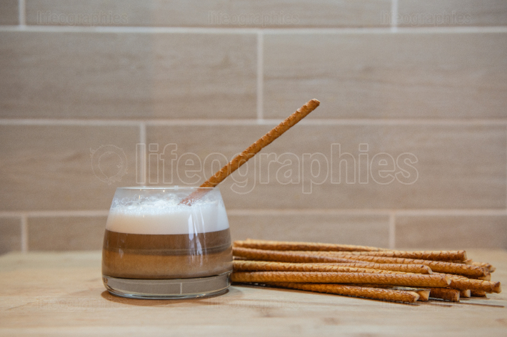 Multilayer coffee or cappuccino in a glass cup with bread straw
