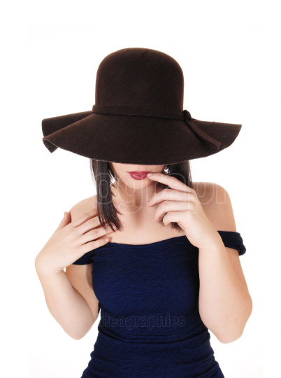 Mysterious woman with big brown hat in close up