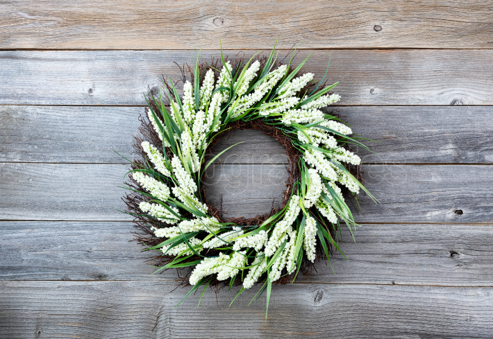 Natural flower wreath on weathered wooden background