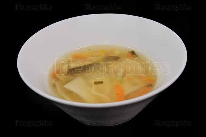 Noodle soup with vegetables on a black