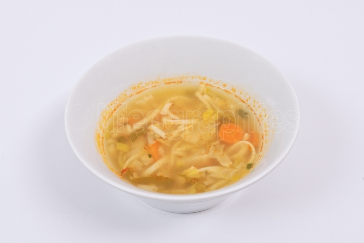 Noodle soup with vegetables on a white
