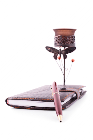 Notebook, pencil and a candle holder