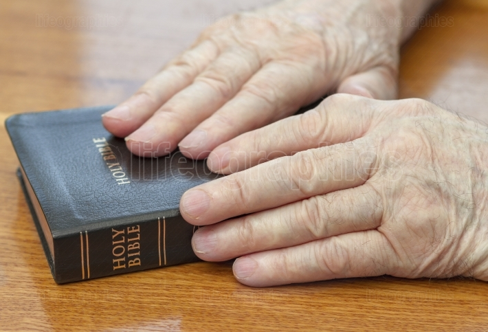 Old man hands on bible