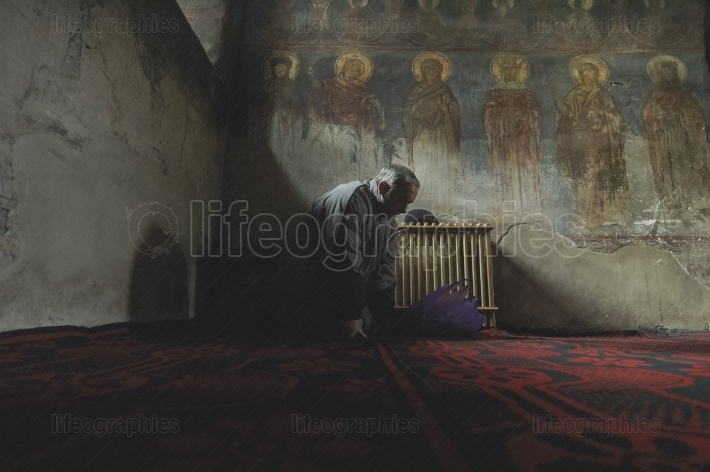 Old man praying in church