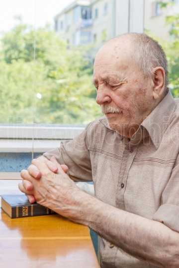 Old man praying with Bible