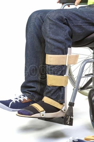 Orthopedic equipment for young man in wheelchair - close up