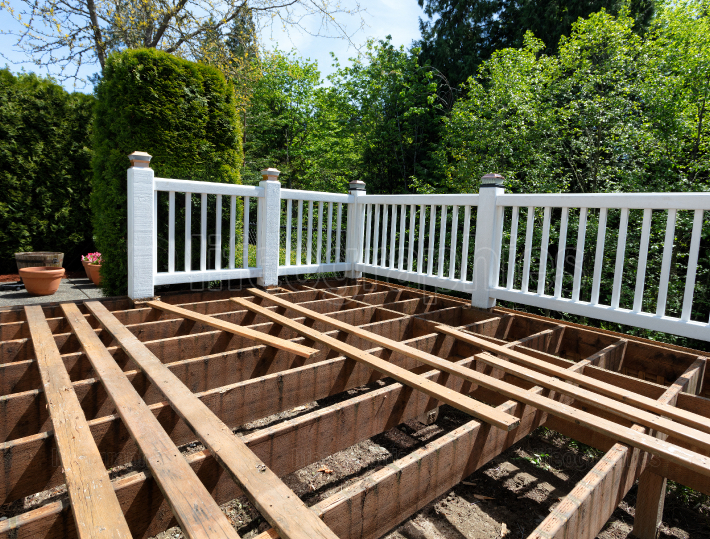 Outdoor exterior wooden cedar deck being remodeled with floor bo