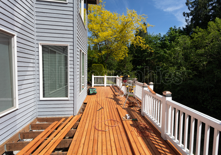 Outdoor red wooden cedar deck being remodeled with new floor boa