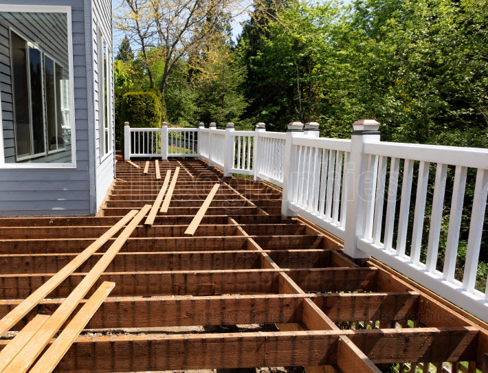 Outdoor wooden cedar deck being remodeled down to structure