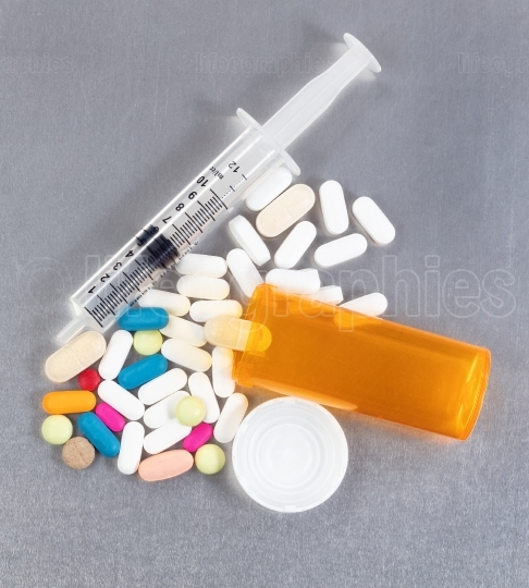 Overhead view of prescription bottle with pills and syringe