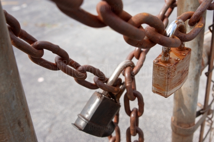 Padlocks And Rusted Chains Secure Gate At Industrial Site