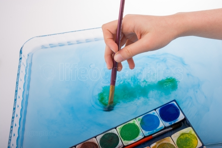 Paint dissolving as painting brush touches water