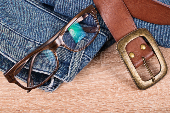 Pair of jeans, glasses and a belt on a table