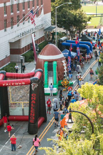 People Participate In Inflatable Games At College Football Fan Fest