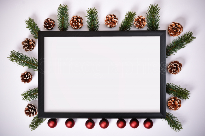 Photo frame with pinecones, evergreen branches and Christmas decoration