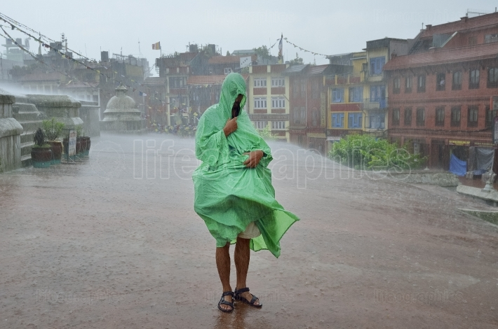 Photographer who protects camera gear becauseof a torrential rain that flowing in the center of boudhanath stupa