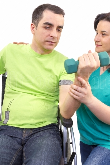 Physical therapist works with patient in lifting hands weights.