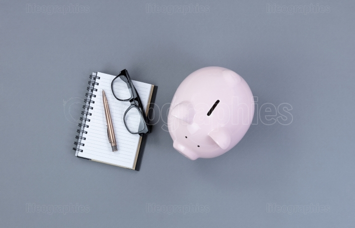Piggy bank and traditional writing materials on gray desktop bac