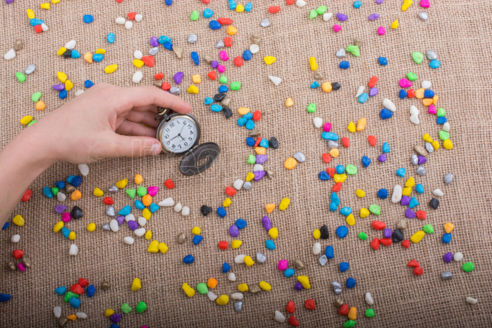 Pocket watch amid Colorful pebbles