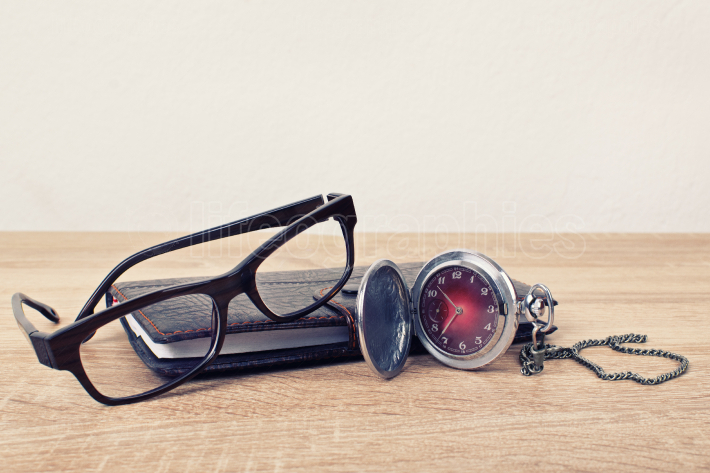 Pocket watch, glasses and a planner on a table