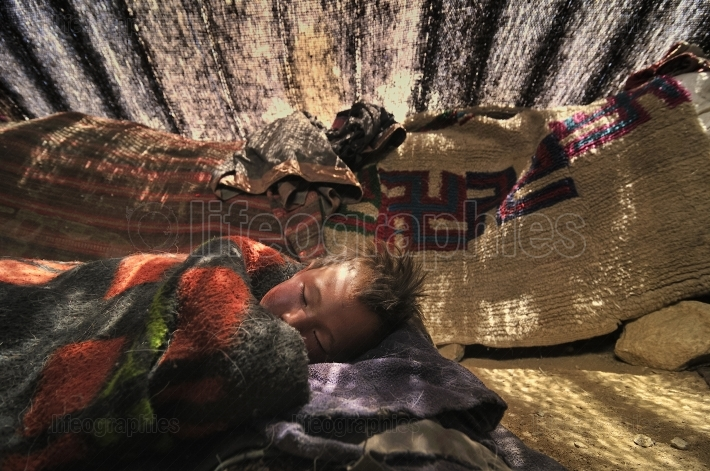 Poor child sleeping on parents nomad tent floor.