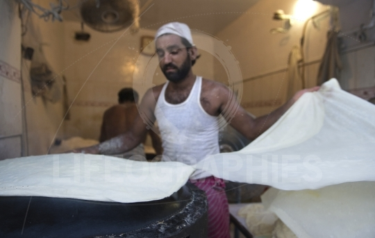 Poor man working in a small bread factory